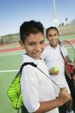 年轻男孩和女孩用网球设备在网球场集中于男孩画象 免版税库存照片