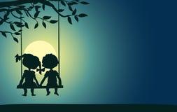 男孩和女孩的月光剪影 免版税库存照片