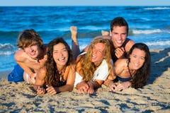 男孩和女孩编组获得在海滩的乐趣 免版税库存图片