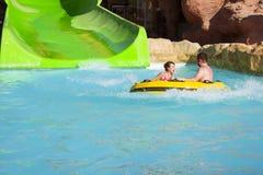 男孩和女孩获得乐趣在度假在幻灯片的在水公园,嘘 免版税库存照片