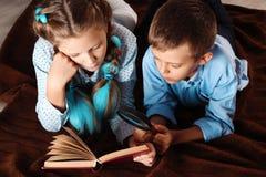 男孩和女孩读一本书 库存图片