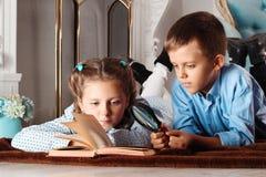 男孩和女孩读一本书 免版税库存照片