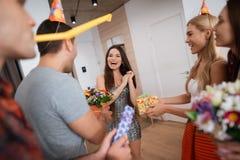 男孩和女孩遇见有礼物的生日女孩 女孩对意想不到的惊奇非常满意 免版税库存照片