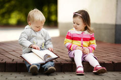 男孩和女孩阅读书 免版税库存照片