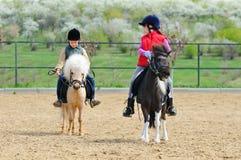 男孩和女孩骑马小马 库存图片