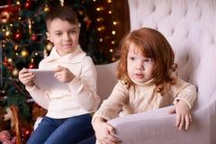 男孩和女孩 圣诞节内部 背景计算机设计例证片剂白色 免版税库存图片