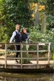 男孩和女孩以维多利亚女王时代的时尚在湖附近在公园 免版税图库摄影