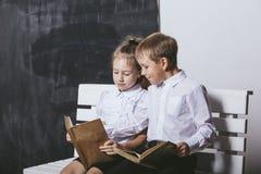 男孩和女孩从小学类在长凳读了书o 库存照片