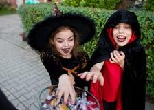 男孩和女孩黑衣服的为万圣夜给手到一个花瓶有甜点的 免版税库存照片