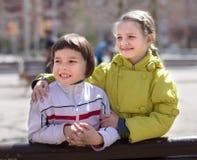 男孩和女孩画象一条长凳的在小阳春 免版税库存照片