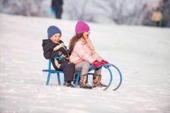 男孩和女孩sledding 库存照片