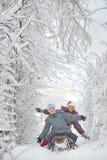 男孩和女孩sledging的 免版税库存图片