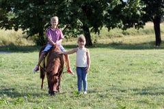 男孩和小女孩有小马马的 免版税库存图片
