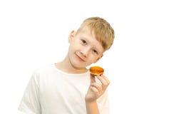 男孩和小的杯形蛋糕在白色背景 免版税库存照片
