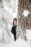 男孩和树在雪 库存图片