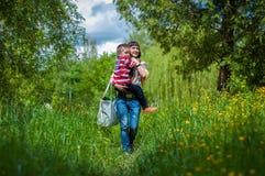 男孩和母亲绿草的 库存图片