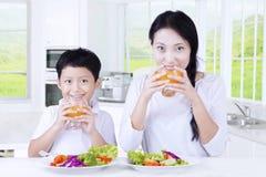 男孩和母亲饮料汁液在厨房里 免版税库存照片