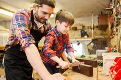 男孩和爸爸有轮尺的在车间测量木头 免版税库存照片