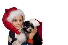 男孩和狗在圣诞老人帽子在圣诞节 免版税库存图片