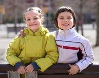 男孩和白肤金发的女孩画象一条长凳的在小阳春 库存照片