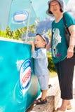 男孩和祖母在冰箱附近有冰淇凌的 库存图片
