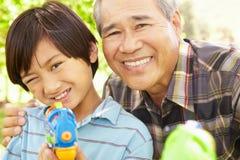 男孩和祖父有水枪的 免版税库存图片