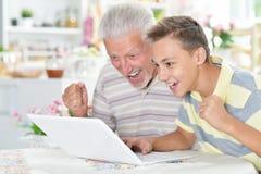 男孩和祖父画象有膝上型计算机的 图库摄影