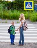 男孩和站立在一条行人交叉路附近的女孩 库存图片
