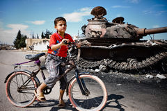 男孩和自行车有T72坦克的,阿扎兹,叙利亚。 库存照片