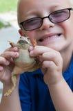 男孩和蟾蜍 库存图片