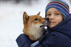 男孩和逗人喜爱的狗在冬天走 库存图片