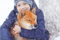 男孩和逗人喜爱的狗在冬天走 免版税库存图片