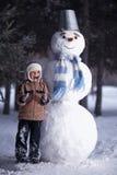 男孩和雪人 图库摄影