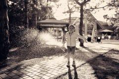 男孩和水浪花  免版税库存照片