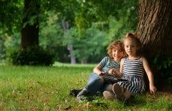 男孩和7-8年的女孩坐在一棵大树下在公园 库存图片