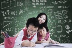 男孩和他的姐妹在与老师的类学习 免版税库存图片