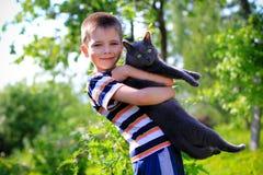男孩和他的宠物猫 免版税库存照片