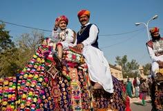 男孩和他的父亲乘坐骆驼 库存照片