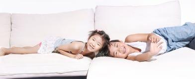 男孩和girlplaying和笑在沙发 免版税图库摄影