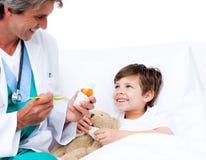 男孩咳嗽一点医学微笑的采取 免版税库存图片