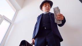 男孩商人sniffes美元和看看巨大的盒钞票在他的手上 股票录像