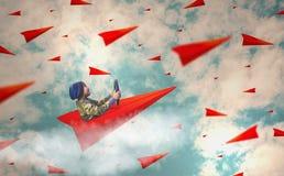 男孩喜欢驾驶纸飞机高昂在天空充满许多纸飞机、概念、视觉和领导带领 免版税库存照片