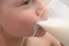 男孩喝从一块玻璃的牛奶早餐 免版税库存照片