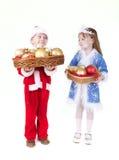 男孩圣诞节给女孩小的玩具穿衣 免版税图库摄影