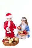 男孩圣诞节给女孩小的玩具穿衣 免版税库存照片
