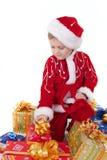 男孩圣诞节给玩具穿衣 免版税图库摄影