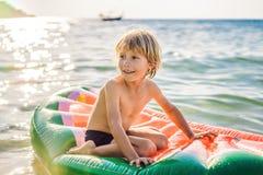 男孩在一个可膨胀的床垫的海游泳 图库摄影