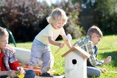 男孩在一个夏天晴天的庭院里做鸟的一个鸟舍 库存照片