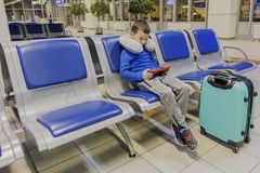 男孩在一个空的机场一等待飞机和戏剧在他喜爱的小配件 图库摄影