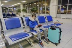 男孩在一个空的机场一等待飞机和戏剧在他喜爱的小配件 免版税库存图片